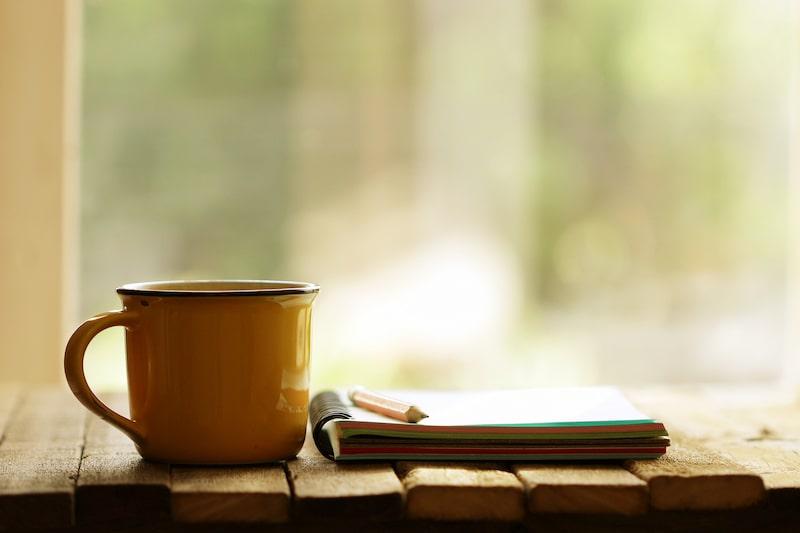 Gartenplan schreiben mit Tasse Kaffee